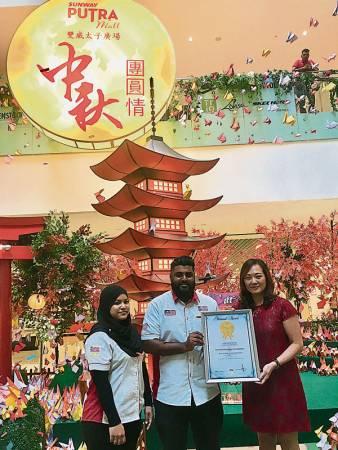 西蒂哈嘉爾(左起)陪同布瓦納斯瓦仁,將《馬來西亞紀錄大全》證書交給潘瑞蓮。