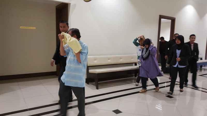 依斯迈阿末(右)和慕希琳(次排右)步出法庭,前者用面巾遮脸,后者则低头快速离开法庭。