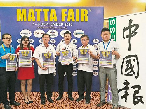 陳允耀(右3)移交《中國報》MATTA旅遊特輯給陳國良(左3)及潘在能(右2)。左起為吳健雄、熊勓妘和王勇添(右)。