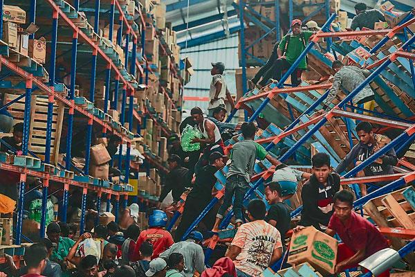 由于居民流离失所,物资补给缓慢,当地居民帕卢在货舱搜刮物资。(路透社)