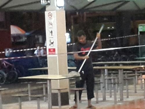 清洁工被拍到在清洗樟宜村小贩中心时,用同一把拖把拖地又抹桌椅。(受访者提供)