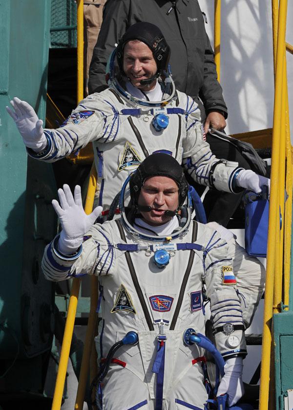 太空人海格(上)和欧夫契宁进入太空船前,先向众人挥手。(法新社)