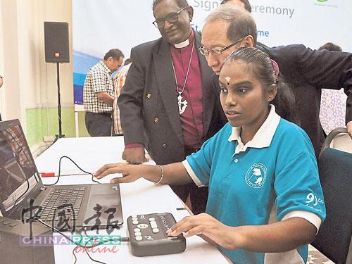 查理斯(左起)及许子根,了解一名视障学生如何使用线上教学系统。