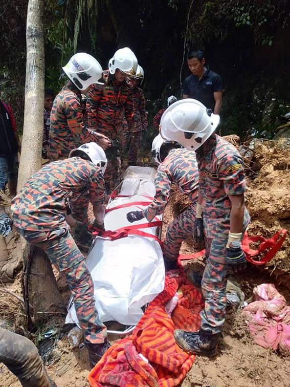 消拯员从泥堆中挖出死者遗体。