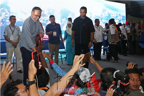 支持者走向舞台与安华握手,恭贺他高票中选。