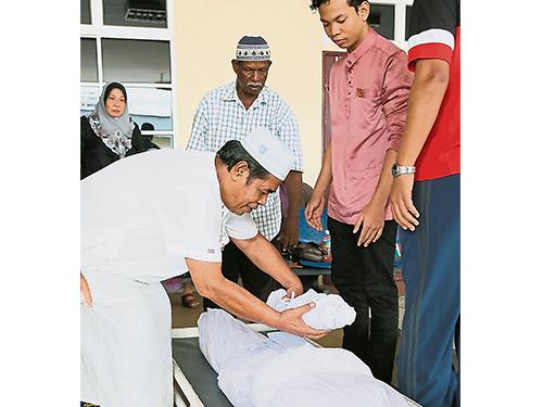 宗教师将男婴遗体置在少女旁,将这对母子遗体送往巴里文打的穆斯林墓地进行葬礼。