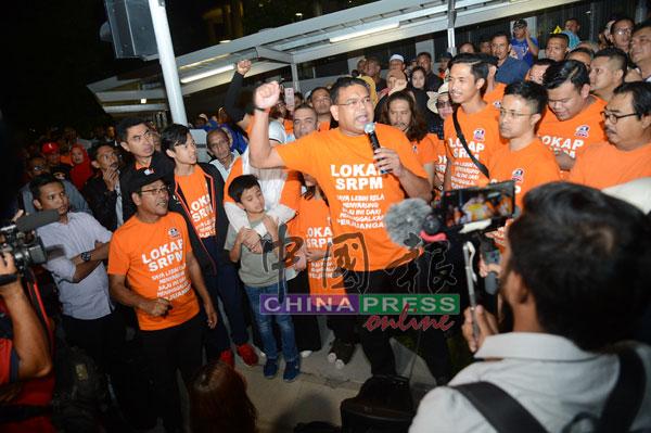 """洛曼(中)向逾150位出席者发言,同时带领他们高喊""""释放扎希""""的口号。"""