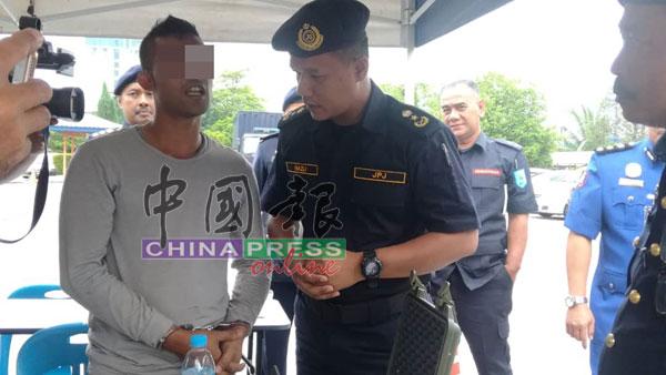 纳兹里(右)向非法驾驶的印尼籍男子(左)进行问话。