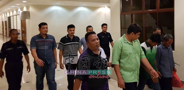 涉嫌亮枪洗劫越南籍渔民的5名被告,由警员押送到关丹法庭面控结伙持械打抢罪名。