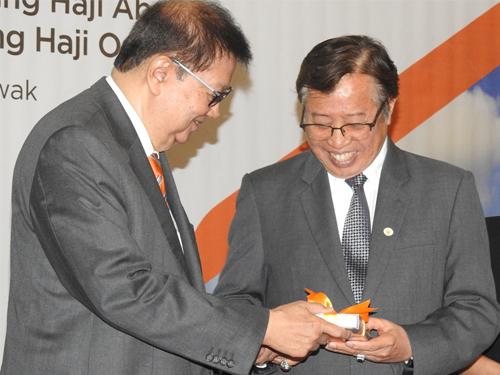 阿邦佐哈里(右)从砂拉越与东协国际论坛大会主席迈克尧手中接过纪念品。