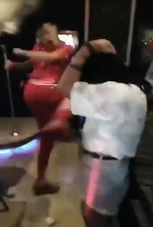 """红衣男利用""""飞毛腿""""踢受害女子的肚子,事后女子抱着肚子蹲下,并发出哀嚎声。"""