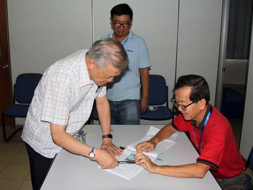 蔡细历(左)凭身分证登记,领取选票。