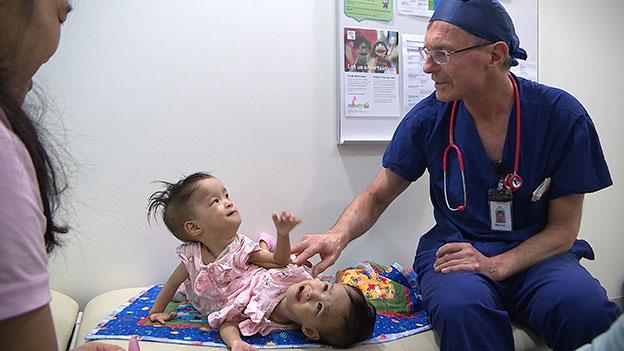 手术前,医生在和小姐妹打招呼。(法新社)