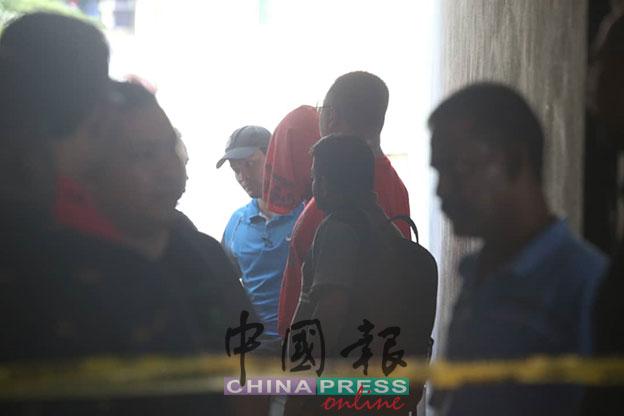 嫌犯头盖着毛巾被警方押返现场。