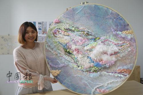 林洁珊热爱创意编织,身边展示的是画面浪漫的创意编织作品《天鹅车站》。