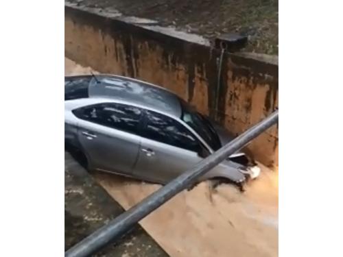 意外坠沟的轿车不敌强力水留,车头的防撞杆几乎脱落。