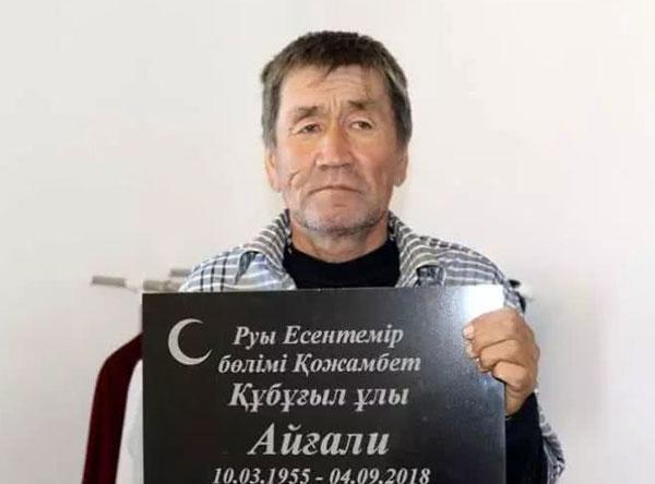 苏普加列夫抱着自己的墓碑拍照。
