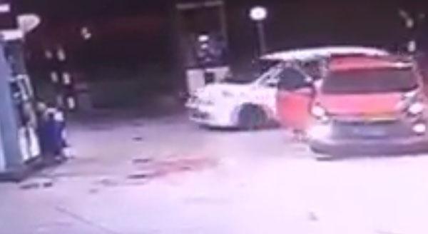 疑在油站外久候多时的白色匪车轿车,相中目标后迅速驶入油站造案。(视频截图)