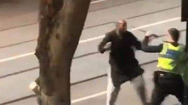 男子持刀企图攻击警员的一幕。