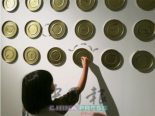 参观者可以随意将江鱼仔贴纸,贴在墙上任何一个角落。