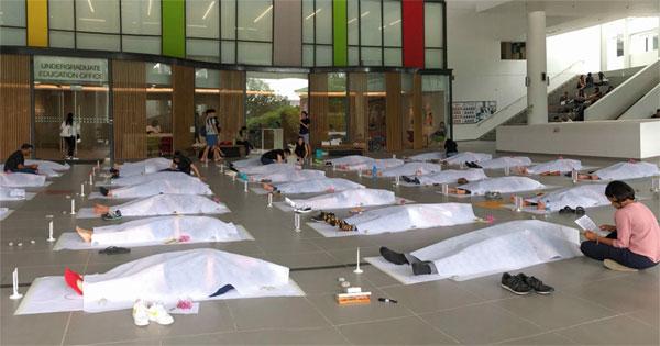 學生們躺在地上,被白布蓋着,進行約30分鐘的模擬喪禮助。