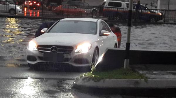 汽车在水中央抛锚,公众将车推到安全的地方。