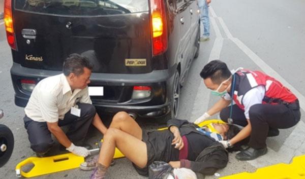 医务人员向疑自行撞车寻死的精神异常孕妇施救准备送院。