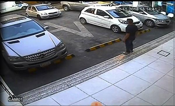 男子欲指挥轿车泊车。