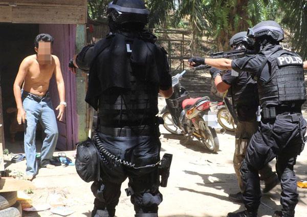 全副武装配备的警员突击上门,一名恐怖分子赤裸上身被捕。