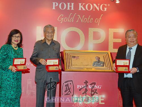 马哈迪(中)推介印有其肖像的特别版金牌。左起为拉菲达和钟义翔。