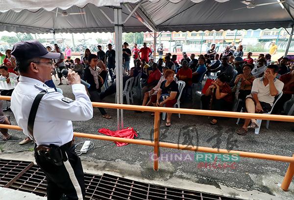 交警在场维持秩序,并念出号码牌,让民众排队缴还罚单。