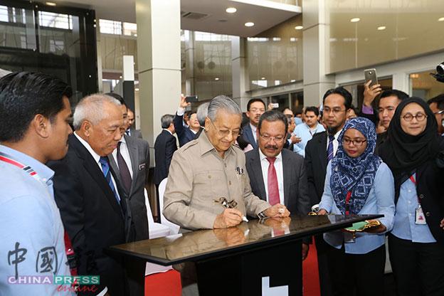 马哈迪(左2)在MIGHT总社纪念牌上签名,左为阿末达祖丁。
