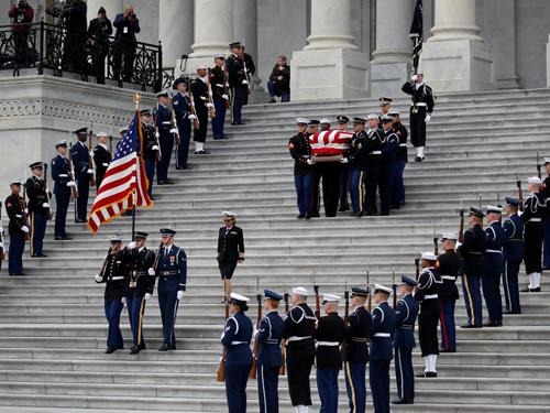 盖着国旗的老布什灵柩昨由三军仪仗队移离国会。