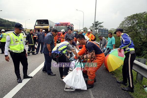 消拯员及警员一起把女死者的遗体包裹后,准备送往医院太平间。