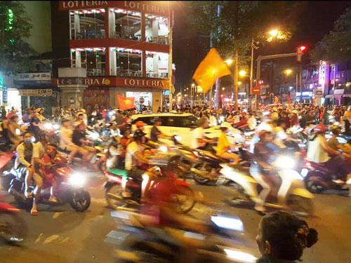 越南国民骑着摩哆手持国旗在高喊口号。