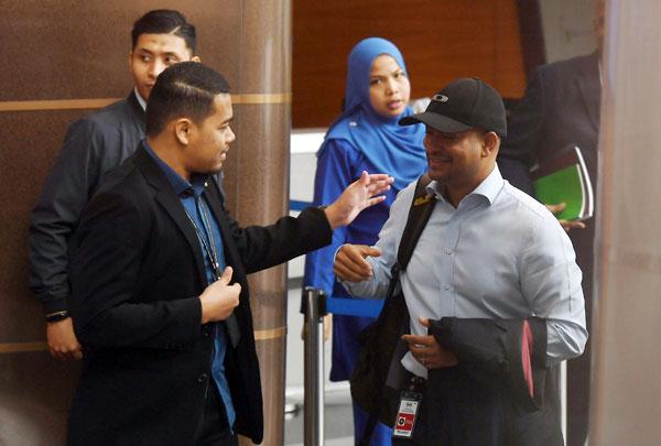 戴着黑帽的阿鲁甘达(右)从后门进入布城反贪会总部,在接待处登记时被媒体发现。