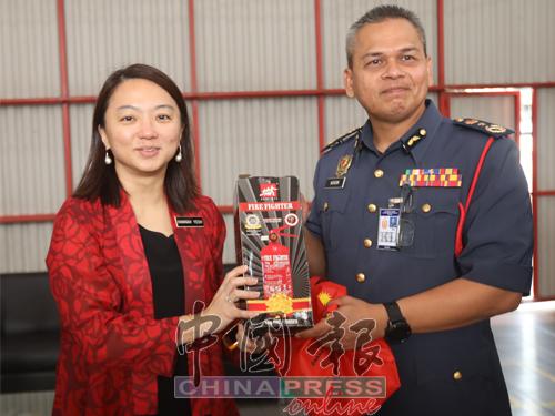 吉隆坡消防局高级助理专员努尔丁帕子(右),赠送纪念品给杨巧双。