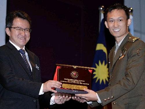 刘镇东(左)在大马武装部队学院的一个颁发文凭仪式上,颁发一个杰出奖项予获奖者。