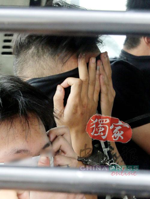 """其中一名嫌犯被警员押上囚车后,还搞怪的以""""OK""""手势拉着上衣掩脸。"""