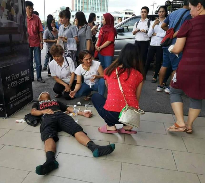 遭爆炸波及一名重伤者被抬到商场外等救护车到来。