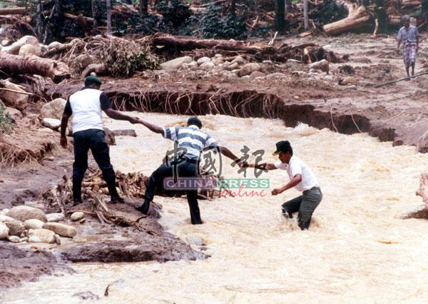 救灾人员守望相助,手拉手越过早已变成泥水的河流。