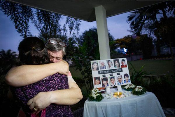 54岁的贾奎伊达在客机失联2周年时,在吉隆坡一座教堂为丈夫帕特里克戈麦斯祈祷时,和1名朋友拥抱。