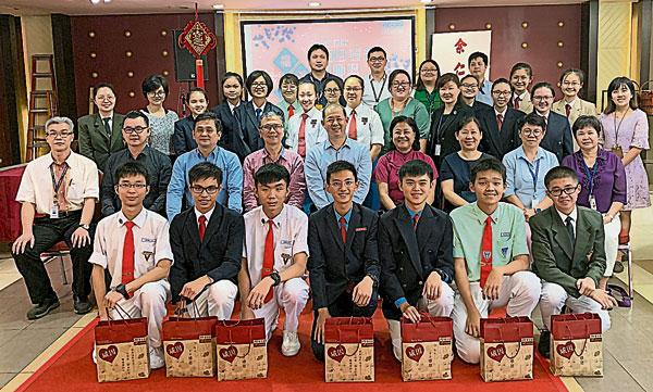 邱月辉(中坐者)与受惠独中的师生代表合照。
