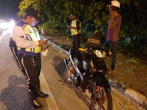 """威北警方交通组逮捕在路上大玩摩哆""""特技""""的马来青年。"""