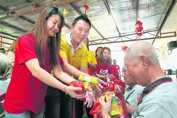郑宇绚(左起)和杨绪坚一起分派物品给长者。
