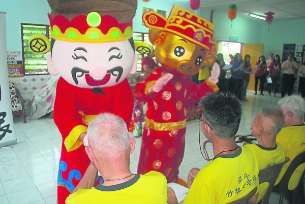 财神爷与金猪吉祥物与老人们分享新春喜悦。