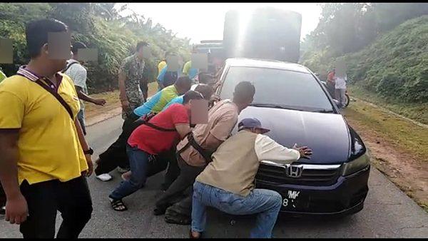 视频中,可见约10人合力掀翻车子。