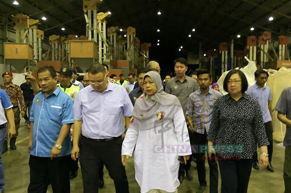 祖莱达(左3)在阿兹曼(左起)、林桂亿等陪同下突击检查非法再循环塑料厂,背景为大型机器。