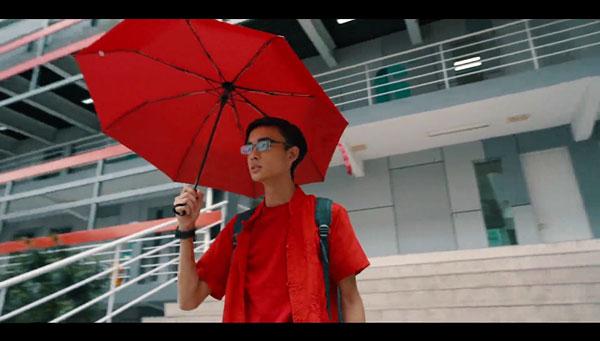"""饰演主角的""""小明""""听信""""陈师傅""""所言购买了""""888幸运宝盒"""",穿上红衣撑起红伞。"""