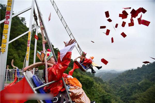 工作人员坐在秋千上大洒红包。